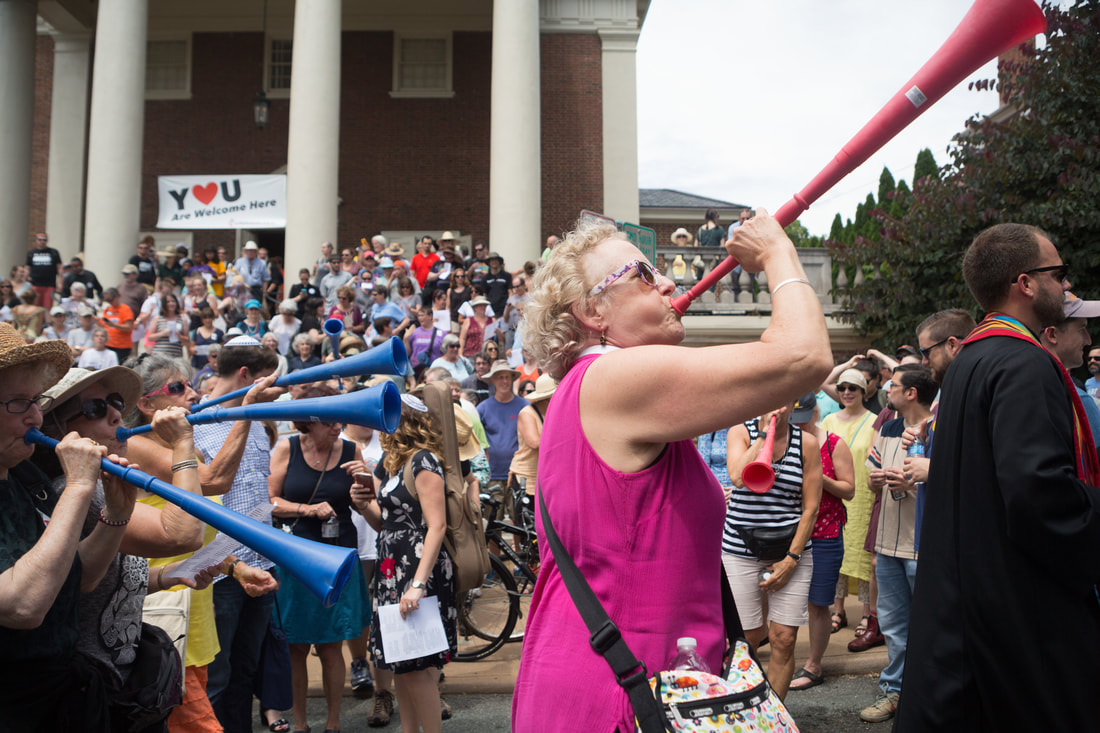 Rev. Elaine Thomas sounds a vuvuzela to lead the march on July 8.